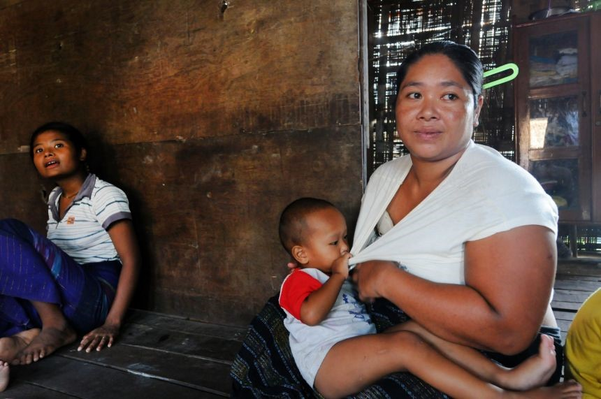 Ei Shel, 30, holds her child in her Hlaing Tharyar home.