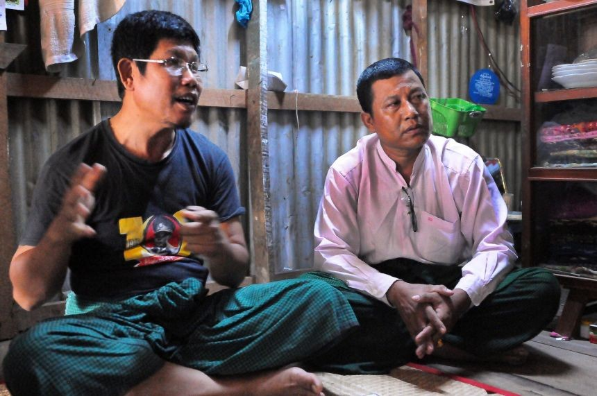 Local National League for Democracy representatives Nyunt Win (wearing Aung San shirt) and Hla Htay sit in the Hlaing Tharyar squatter settlement.